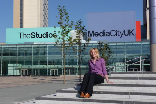Angela Stevenson, wearing a purple top with black trousers, sitting on the steps outside the main TV studio block at MediaCity UK
