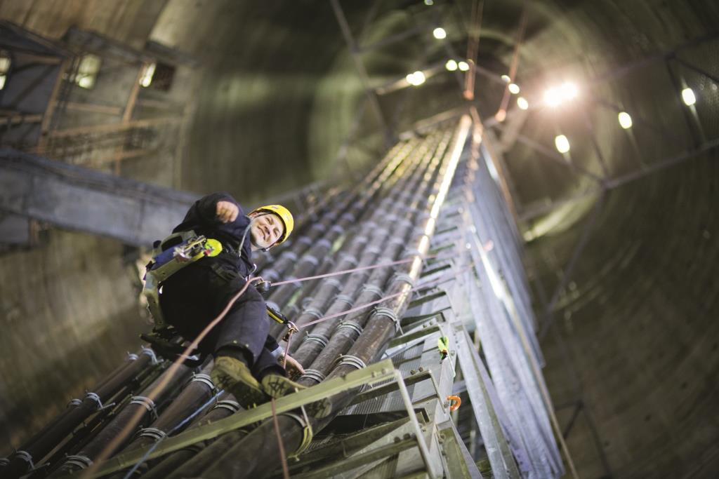 A worm's eye view of a man in abseiling harness and a yellow hard hat with a very large and sliver transmission tower stretching up towards the sky and circle of light above him.