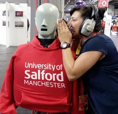 Philippa wearing headphones and shouting into the ear of a grey mannequin wearing a red University of Salford Manchester t-shirt