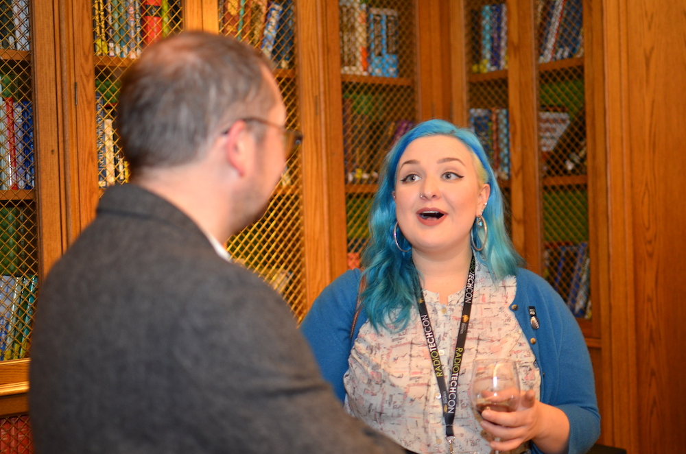 Lady with blue hair chatting to man in grey suit at Radio TechCon