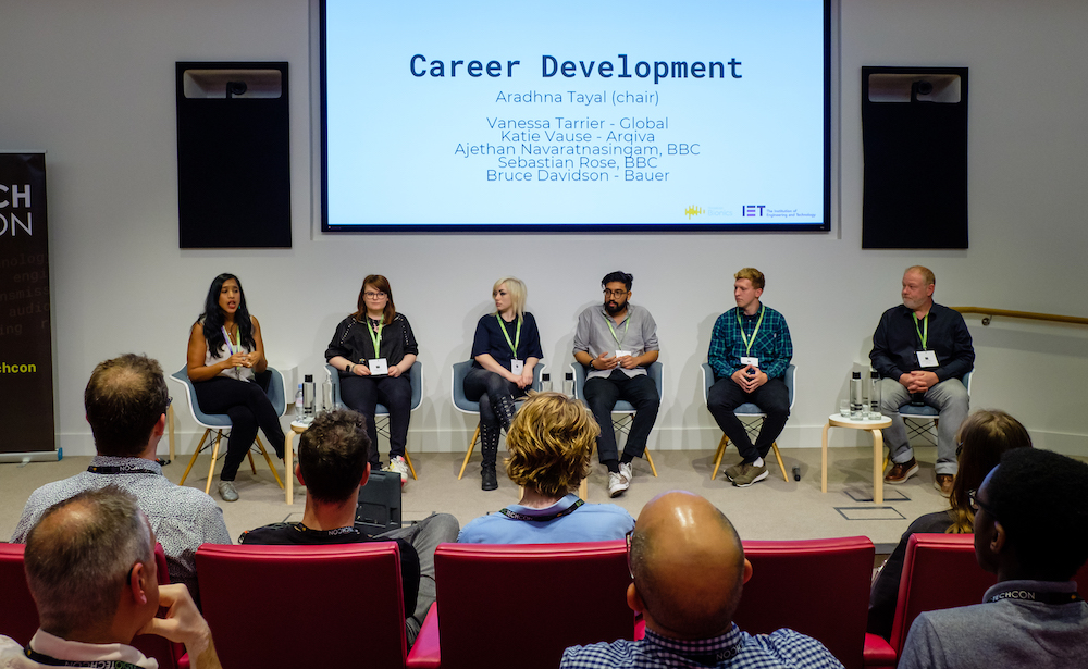 Six people - a mixture of women and men of different ethnicities - sit in front of a sign which says 'Career Development'. The back of the audience's heads are in the foreground.