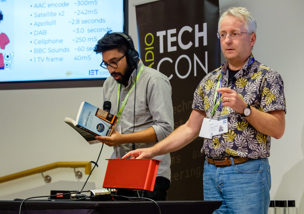 Two men are on stage in front of a Radio TechCon banner. There is a red box on the table. The man on the left is Asian and is wearing headphones. He is holding a microphone and reading an extract from the book 'How To Make Great Radio'. The man on the right is white and has grey hair and a brightly patterned shirt. He is demonstrating the controls of the red audio delay box.