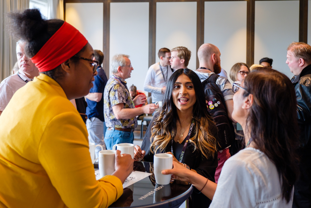 A black woman wearing a yellow top and a red headband, an Asian woman with hair which is ginger at the bottom, and another woman with brown hair who has her back to the camera, laugh over coffee at the Radio Technology Masterclass. Other delegates can be seen chatting in the background.