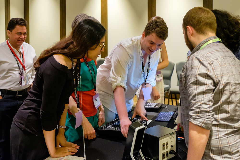Delegates peering at a piece of studio equipment at the Radio Technology Masterclass