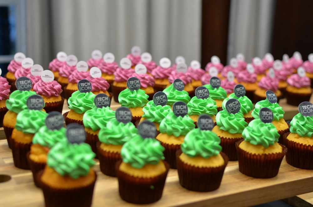 Cupcakes with bright pink icing and a white Broadcast Radio logo in the background, and cupcakes with bright green icing and a black Radio TechCon logo in the foreground