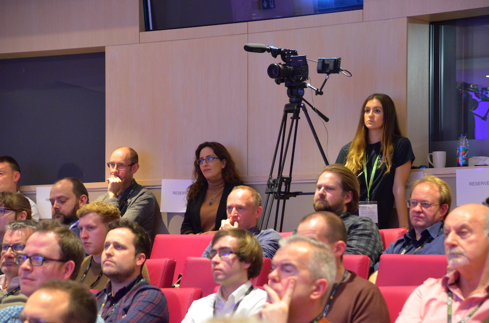 A camera on a tripod at the back of the Radio TechCon auditorium