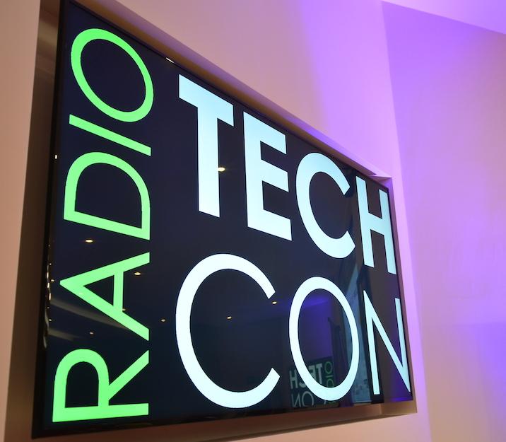 Radio TechCon sign at jaunty angle with purple uplighter