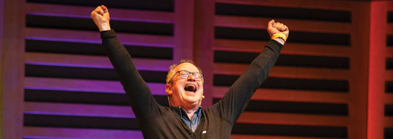 Robin Ince with hands stretched above his head in a V shape.