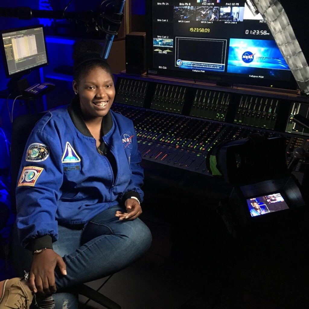 Alexandria Perryman wearing a blue Nasa jacket and sitting in front of a sound console with Nasa logos on the monitors behind her.
